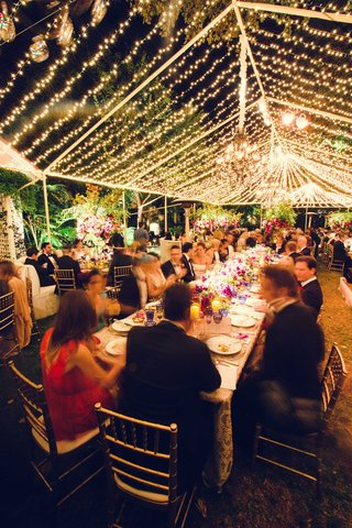 wedding-reception-guests-at-long-family-table-under-tent-lined-with-string-lights