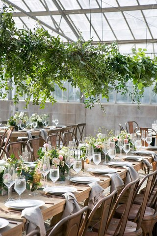 wedding-reception-wood-table-industrial-chairs-low-centerpiece-overhead-greenery-greenhouse-venue