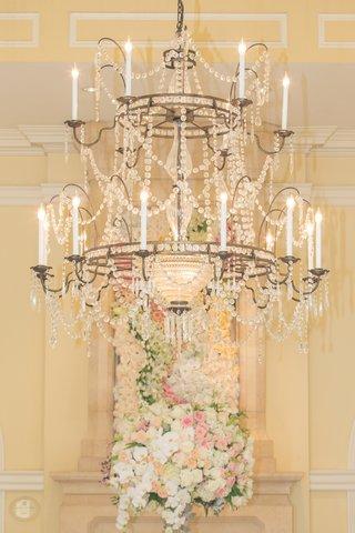 wedding-reception-with-crystal-chandelier-arrangement-of-white-pink-light-orange-roses-orchids