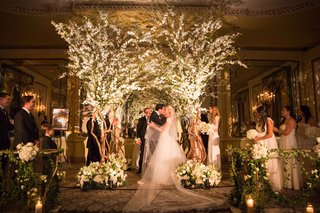 bride-and-groom-share-first-kiss-under-chuppah-looks-like-trees-with-branches-foliage-white-flowers