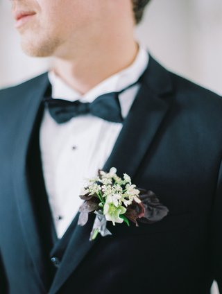 groom-in-a-three-piece-black-tuxedo-suit-boutonniere-of-small-white-flowers-purple-leaves-verdure