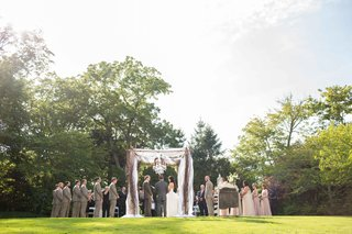 a-couple-with-their-bridal-party-on-either-side-getting-married-under-alfresco-arbor