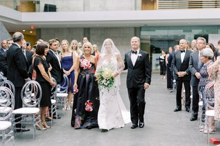 bride-with-veil-over-face-walking-down-aisle-with-mother-in-flower-print-one-shoulder-gown-father