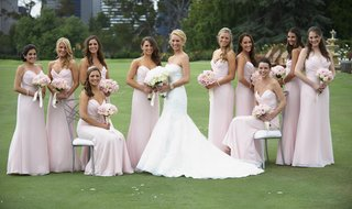 bride-in-fit-and-flare-gown-with-bridesmaids-in-pink