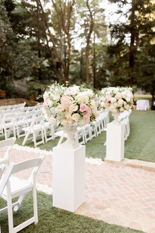calamigos-ranch-wedding-white-pillar-with-ivory-florals-brick-aisle