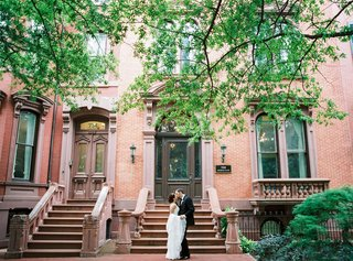 bride-in-wedding-dress-from-the-white-dress-kissing-groom-in-front-of-brownstone-building-dc
