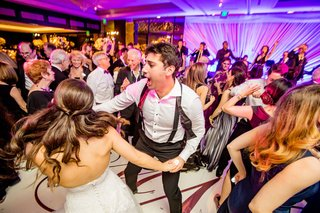 bride-and-groom-dancing-on-dance-floor-with-rose-gold-monogram-purple-pink-lighting-live-band