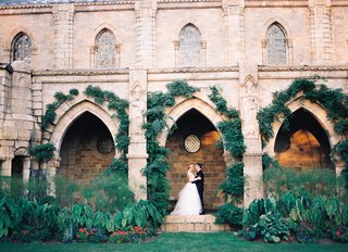 bride-and-groom-posing-under-arches-of-bryn-athel-cathedral