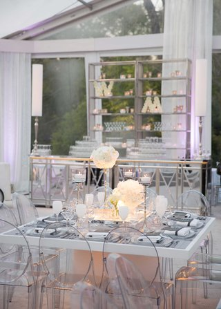 white-square-table-with-grey-decor-ghost-chairs-and-white-goblets-with-ivory-centerpiece-flowers