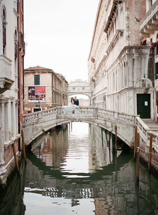 bride-and-groom-on-bridge-in-venice-italy-canals-historic-buildings-floating-city-destination