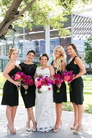 a-bride-in-lace-gown-with-bridesmaids-in-assorted-black-cocktail-dresses-bright-pink-purple-bouquets