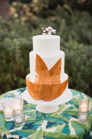 white-wedding-cake-with-copper-leaf-decoration-dog-cake-topper