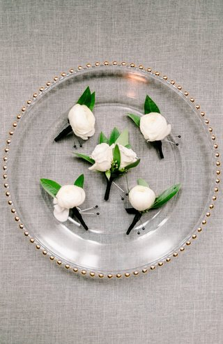 five-boutonnieres-with-a-single-white-flower-and-two-green-leaves-on-glass-charger-plate-with-gold-t