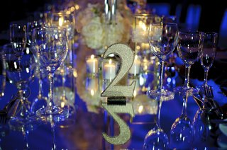 gold-glitter-table-number-two-at-wedding-blue-lighting