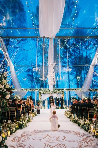 wedding-ceremony-winter-blue-outdoor-clear-tent-white-drapery-chandelier-lights-greenery-gold-runner