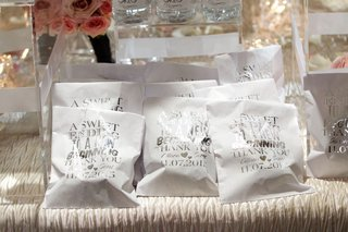 white-wedding-favor-bags-with-silver-lettering-filled-with-sweet-treats-donuts-dessert-favor-ideas