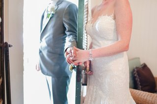 bride-and-groom-hold-hands-around-a-door-before-ceremony-bride-in-diamond-bracelet