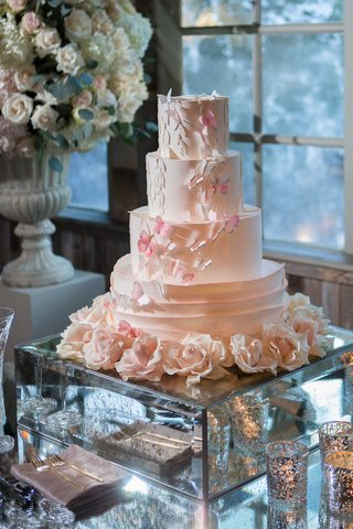 wedding-cake-on-mirror-stand-sugar-flowers-tiers-with-pink-butterfly-designs-urn-with-flowers
