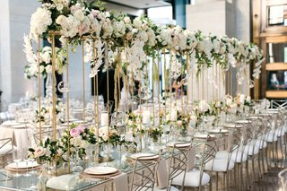 long-glass-tables-with-a-floating-garland-runner-on-thin-gold-stands