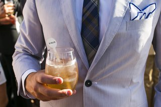 groomsman-holding-cocktail-with-swizzle-stick