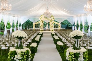white-drapes-tent-wedding-with-green-hedge-and-white-rose-decor-chuppah-gold-chairs-chandeliers