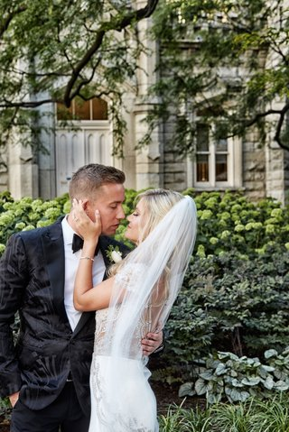 bride-in-jeweled-wedding-dress-from-bella-bianca-couture-veil-blonde-hair-kissing-groom-in-tuxedo