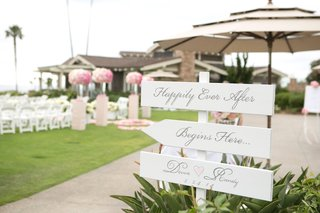 white-wood-arrows-pointing-toward-wedding-ceremony