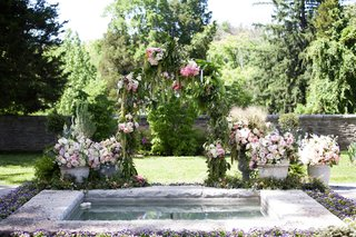 a-custom-secret-garden-inspired-arch-with-dripping-greenery-and-pink-and-purple-flowers