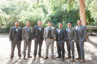 groom-in-light-grey-suit-with-groomsmen-in-grey-suits-and-bow-ties-brown-shoes-rustic-wedding