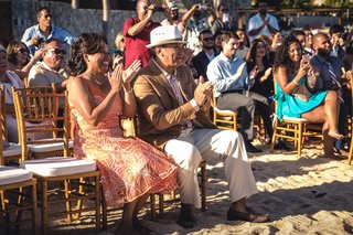 friends-and-family-as-wedding-guests-clapping-for-the-newlywed-couple-during-their-beach-ceremony