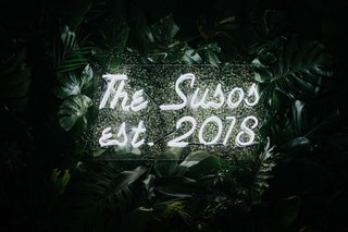 wedding-reception-decor-palm-frond-jungle-leaf-backdrop-with-lucite-neon-sign-couple-new-last-name