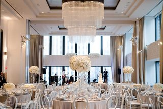 wedding-reception-ballroom-view-of-chicago-chandelier-white-flower-arrangements-light-grey-linen