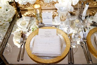gold-rim-charger-plate-with-sparkly-napkin-menu-tucked-in-mirror-table-with-white-ranunculus-flowers