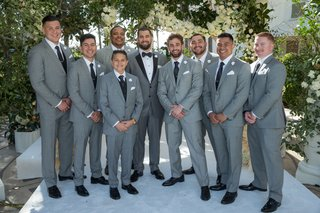 groom-in-grey-suit-with-groomsmen-in-similar-light-grey-suits-black-shoes-and-ties-white-pockets