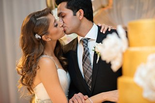 bride-with-curled-hair-and-sparkling-brooch-kisses-groom