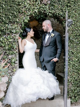 bride-in-ines-di-santo-wedding-dress-v-neck-fit-and-flare-gown-with-full-ruffles-groom-in-tuxedo