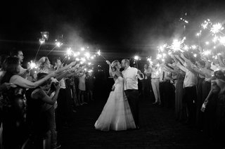 black-and-white-photo-of-bride-and-groom-kissing-during-sparkler-exit-holding-sparklers-guest-tunnel