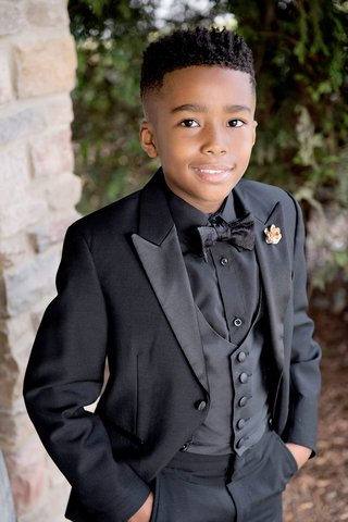 young-ring-bearer-posing-for-photo-in-tuxedo-black-jacket-vest-shirt-and-bow-tie-slacks
