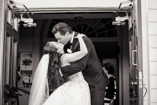 black-and-white-photo-of-bride-and-groom-kissing-on-outside-of-church-doors-after-ceremony-veil-long