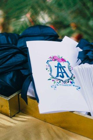 wedding-ceremony-program-next-to-midnight-blue-yarmulkes-in-gold-tray