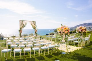 wedding-ceremony-yellow-flower-petal-aisle-arch-ocean-view-ceremony-chameleon-chair-collection-chair
