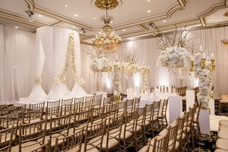 wedding-ceremony-ballroom-the-legacy-castle-white-gold-decor-drapery-flowers-candelabra