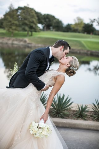 groom-in-tuxedo-with-bow-tie-kisses-bride-in-champagne-monique-lhuillier-wedding-dress