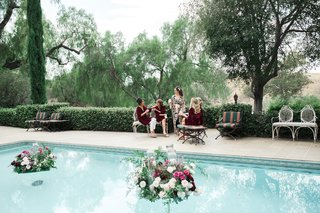 bride-in-flowy-floral-robe-bridesmaids-in-burgundy-velvet-robes-pool-with-floating-florals