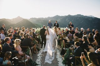 bride-in-strapless-romona-keveza-wedding-dress-sweetheart-neckline-walks-down-aisle-with-parents