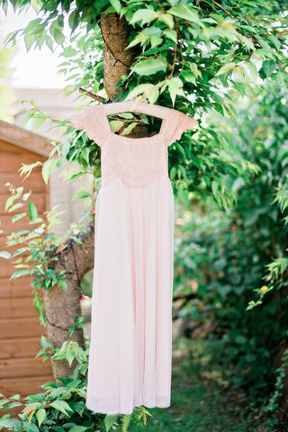flower-girl-dress-cap-sleeves-details-blush-hanging-up-garden-outside-english-wedding-british