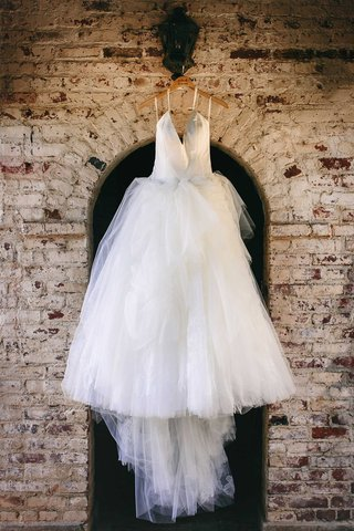white-tulle-ball-gown-with-plunging-halter-neckline-hanging-up-before-ceremony