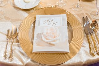 wedding-guest-place-setting-with-gold-charger-gilt-flatware-silverware-and-single-white-rose-on-menu