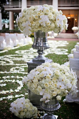 white-ceremony-flower-arrangements-of-orchid-rose-hydrangea-flowers-in-silver-urn