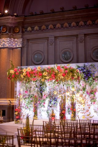 wedding-ceremony-with-colorful-vibrant-flowers-in-chuppah-lucite-column-backdrop